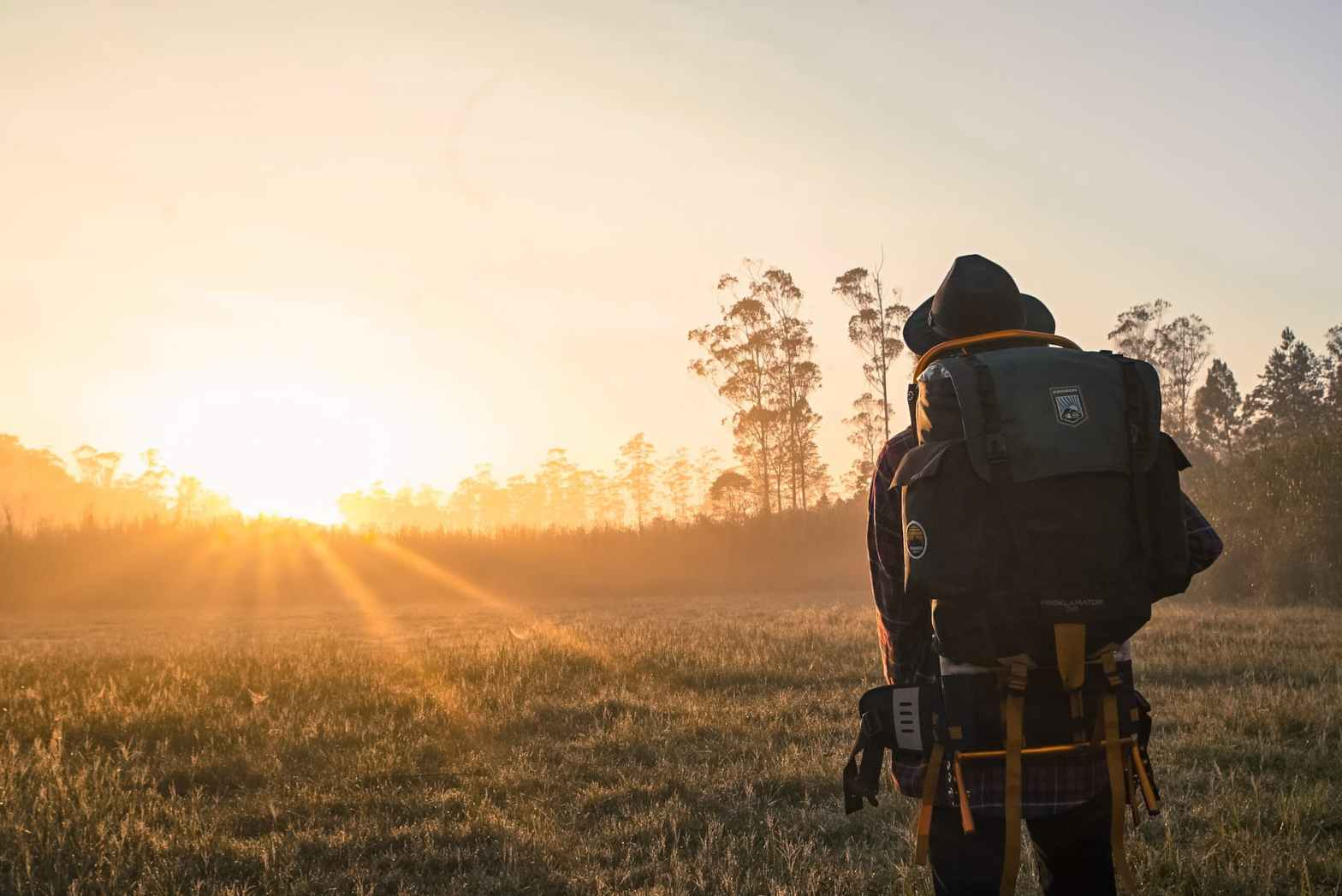 man in black backpack during golden hour