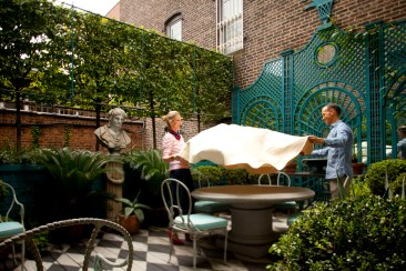 PHOTO: Danielle Rollins and Miles Redd hold a tablecloth over his stone circular garden table.