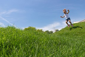 PHOTO: A little girls jumps on the rolling hills at the Nature Play Garden.