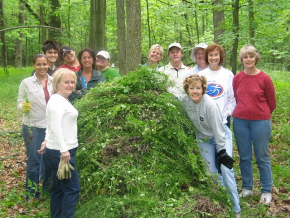 "Garden volunteers pose with a pile of removed garlic mustard at an annual ""garlic mustard pull"" event."