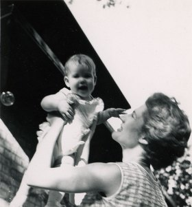 PHOTO: Mom holds her smiling baby daughter in the air.