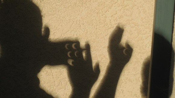 Eclipse shadows seen through crossed fingers of kids.