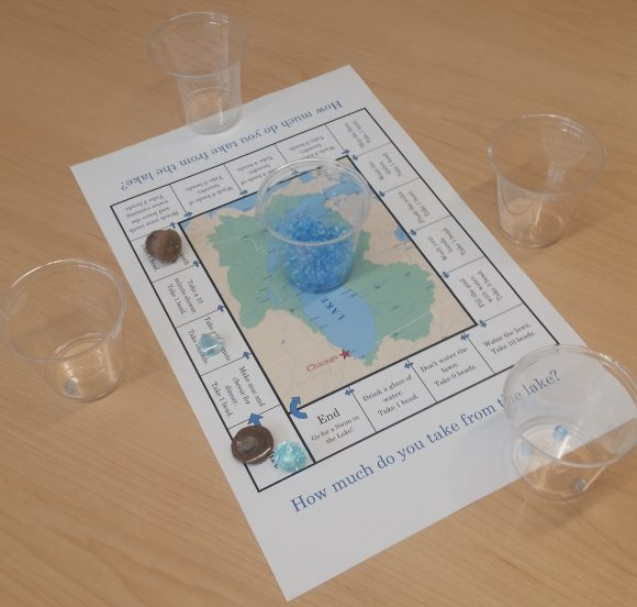 PHOTO: Board, cups, beads, and game tokens are arranged for the water conservation game.