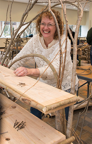 A happy Bim WIllow student works on her rustic shelf from an earlier workshop.