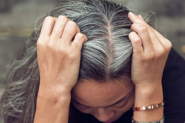 woman parting her gray hair down the middle