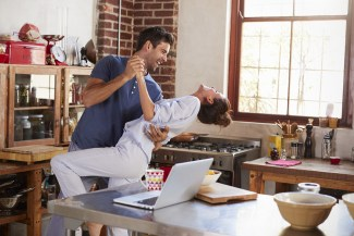 Man and woman, free from financial struggle, dancing happily in their kitchen