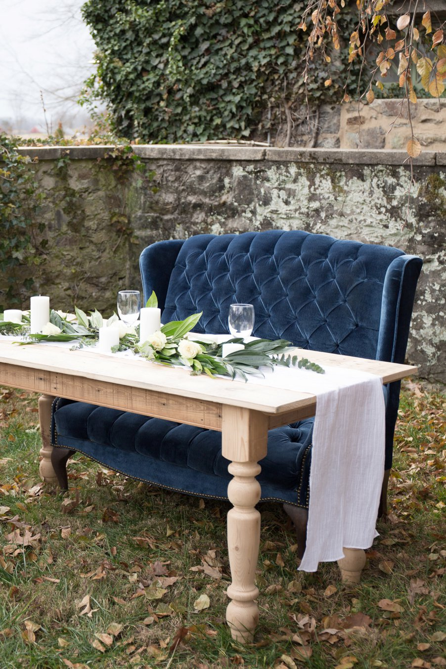 Navy-colored vintage settee sitting behind farm table