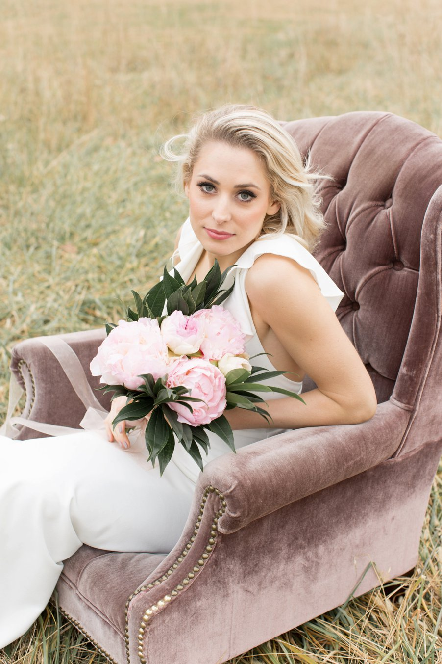 Bride sitting in amethyst-colored vintage chair