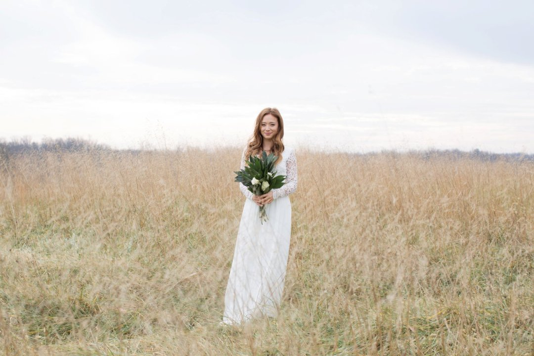 Bride holding bouquet and standing in field