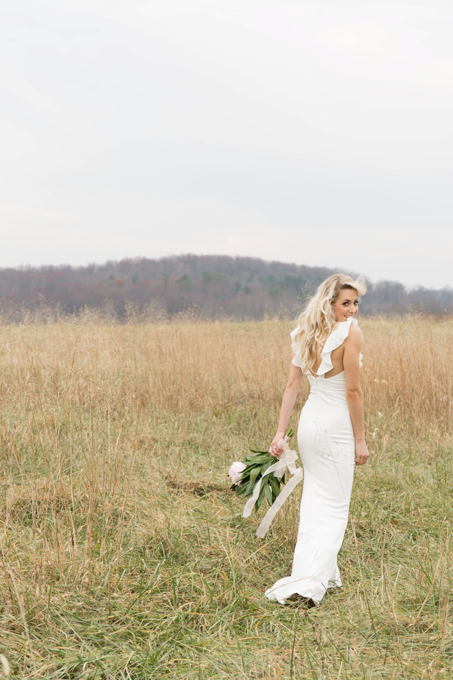 Woman in white wedding dress in a field