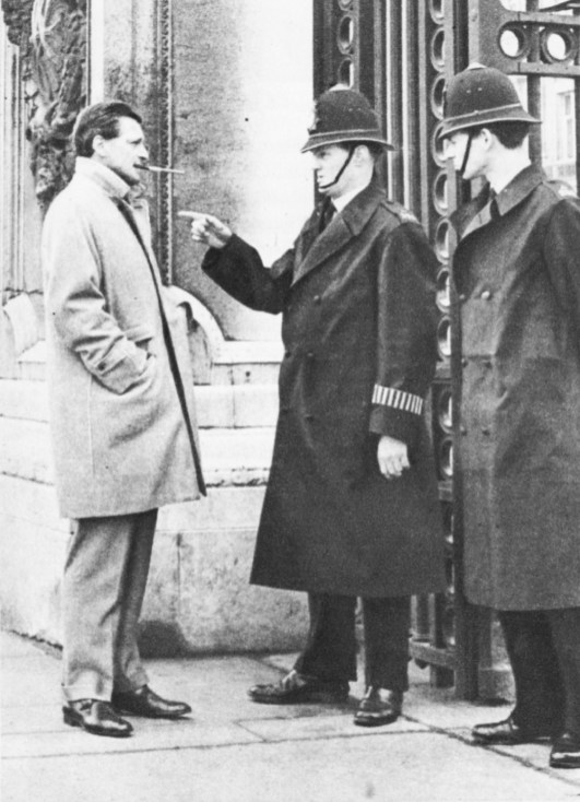 Carlos talks to London policemen at the gates of Buckingham Palace