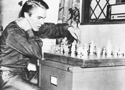 "ADAM FAITH relaxes over the chessboard. Perhaps he has been watching ATV's ""Chess Masterpieces"" and wants to try a move for himself"