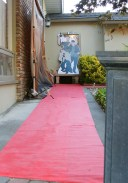 Red carpet welcomes guests. A photographer took pictures as they arrived.