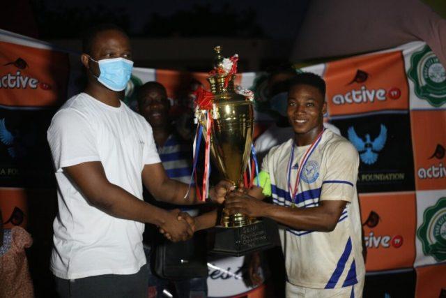 Captain of Kingdom FC receiving the trophy from Mr Precious Senafiawo, CEO of Sena Foundation