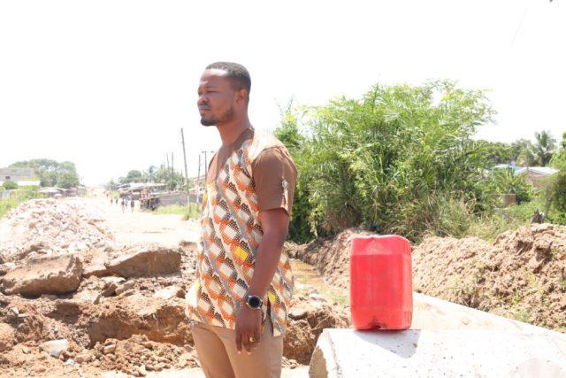 Mr Precious Senafiawo observing the progress of the work on the road.