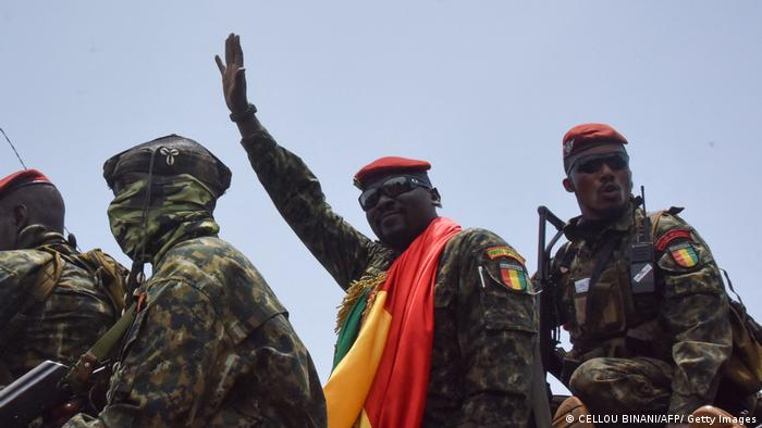 Mamady Doumbouya saluting from the top of a military truck