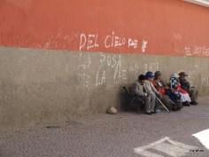 Men sitting on bench along Calle Indaburo.