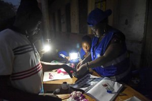 Ghanaian election officials use a lantern and a smartphone torchlight to assist people voting late at a polling station in Tamale this month. Credit Pius Utomi Ekpei/Agence France-Presse — Getty Images