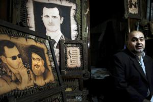 A Syrian shopkeeper waits for customers next to paintings of of President Bashar Assad and Hezbollah leader Sheikh Hassan Nasrallah at the Souk Tawil market in Damascus, Syria, in February. Turkey said on Dec. 29, 2016, that Hezbollah, which has sent thousands of fighters to support Assad, should withdraw from Syria. (Hassan Ammar / AP)