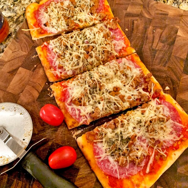 Flatbread pizza with cheese, salami, sausage and oregano, on a cutting board.