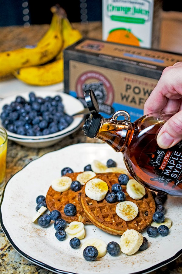 Pouring Aldi maple syrup over protein waffles.