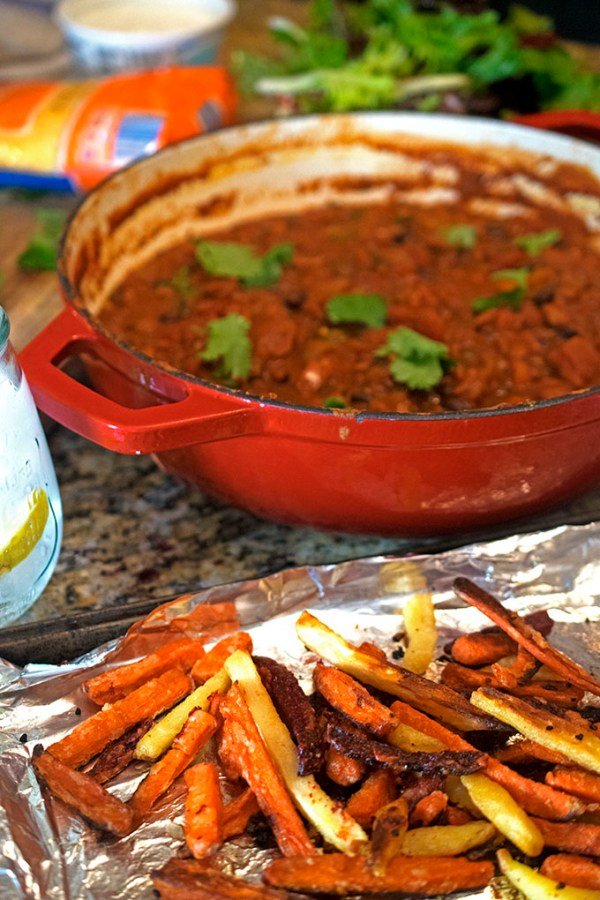 Pot of chili with root vegetable fries on a baking sheet.