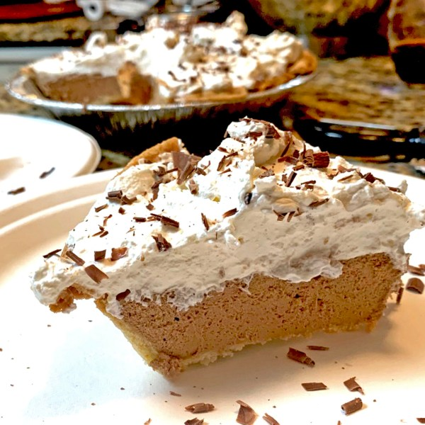 Slice of French silk pie on a serving plate with shaved chocolate on top.
