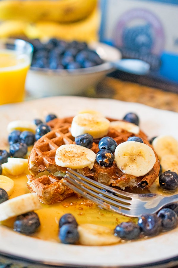 Plate of Aldi power waffles with blueberries, banana slices and maple syrup.
