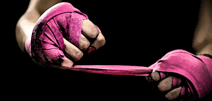 woman wrapping hands with pink boxing wraps. ready for fight