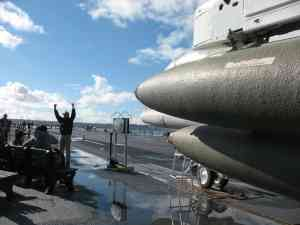 A tour guide gesturing aboard the USS MIdway
