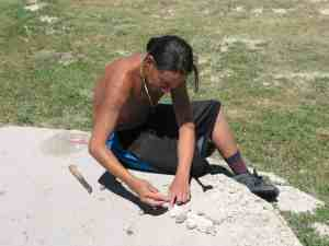 Young Sioux man cleaning a rattlesnake skin