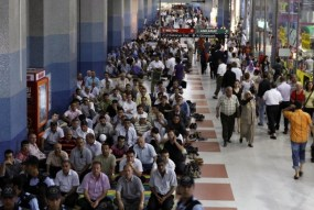 Worshippers attend Friday prayers as commuters walk past at the Kizilay Station of the Ankara metro network in Ankara July 31, 2009. REUTERS/Umit Bektas