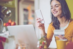 Woman holiday shopping online using a laptop and a credit card