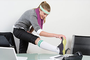 Young woman in workout attire performing a calf stretch on her desk at work