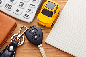 Car keys, calculator, and loan paperwork on a desk