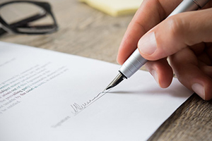 close-up of a person's hand as they are signing a legal document