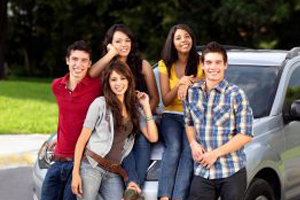 group of multi-ethnic, multi-gender college-agedteens in front of white SUV
