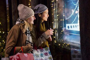 Two young ladies holiday window shopping on a winter evening