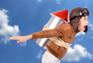 Boy wearing aviator helmet with rocket strapped to back launching into cloud filled sky.