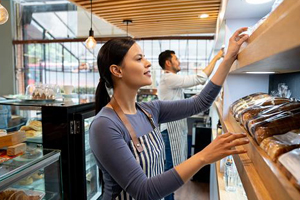 Young female at a retail bakery shop pulls fresh bread off shelf for a customer