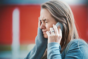 woman visibly upset and closing eyes while on the phone