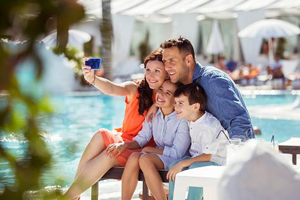 young parents with two kids taking a selfie picture while on vacation
