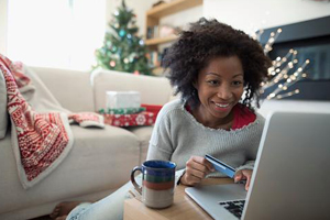 Middle aged black woman holiday shops online from the comfort of her cozy living room