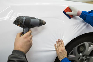 Two auto-body techs apply a vinyl wrap to a car fender