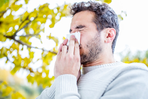 Young man with a tissue to his nose after sneezing due to allergies