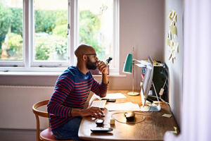young man working from home at his computer