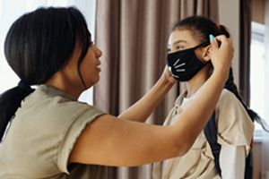 woman putting on young girls face mask