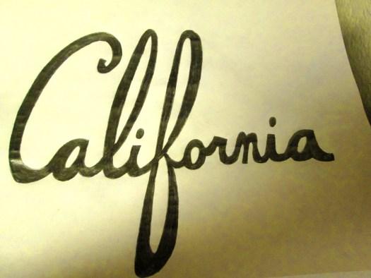 Writing California in cursive block letters.