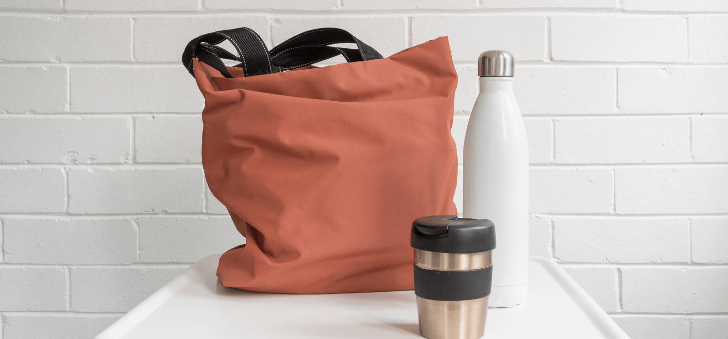 reusable plastic free bag, coffee mug, and water bottle on the kitchen counter