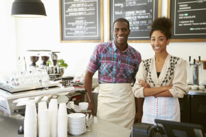 Female Owner Of Coffee Shop With Male Employee